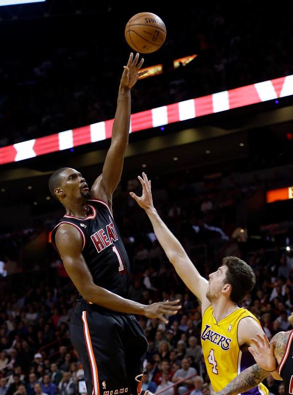. Miami Heat center Chris Bosh (1) shoots against Los Angeles Lakers forward Ryan Kelly (4) during the second quarter of an NBA basketball game in Miami, Thursday, Jan. 23, 2014. (AP Photo/Alan Diaz)