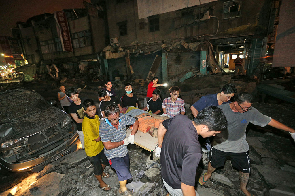 . The body of a victim killed in a gas explosion from an underground gas leak is carried from the rubble in a main street in Kaohsiung, Taiwan, early Friday, Aug. 1, 2014.  A massive gas leakage early Friday caused five explosions that killed several people and injured over 200 in the southern Taiwan port city of Kaohsiung. (AP Photo)