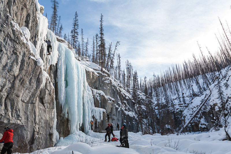 A group of ice climbers stands around a frozen waterfall