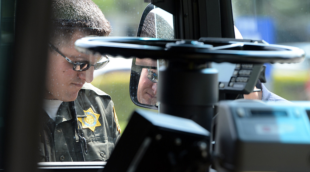 . Mike Russ, a San Bernardino Sheriff\'s crime scene investigator, looks over an OmniTrans bus that was struck by gunfire during an officer involved shooting in San Bernardino May 9, 2013. Two suspects in a Yucca Valley homicide led authorities on a high-speed chase Thursday that ended with a gun battle, one suspect dead, another wounded and a California Highway Patrol officer wounded. The CHP didn\'t say where the bullet struck the officer, but said the wound was not life-threatening. (Rick Sforza/The Sun, San Bernardino)