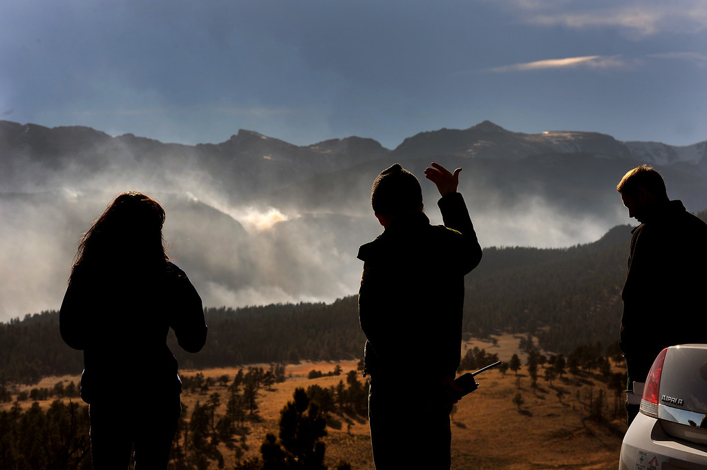 . Larry Frederick, middle, shows the direction of the wind on the Fern Lake Fire. Jake Brollier, another Public Information Officers on the Fern Lake Fire, is at right. Officials worry about winds kicking up later in the afternoon on December 2, 2012.