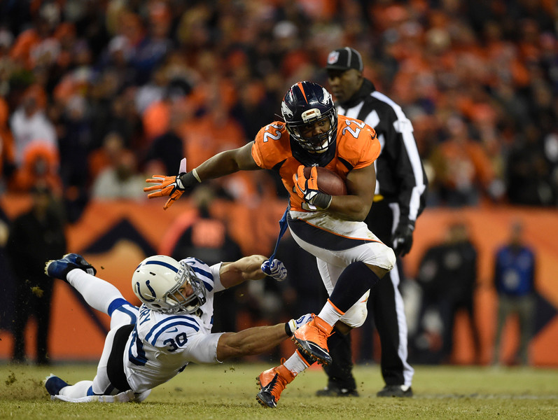 . C.J. Anderson (22) of the Denver Broncos runs for a first down against LaRon Landry (30) of the Indianapolis Colts. The Denver Broncos played the Indianapolis Colts in an AFC divisional playoff game at Sports Authority Field at Mile High in Denver on January 11, 2015. (Photo by AAron Ontiveroz/The Denver Post)
