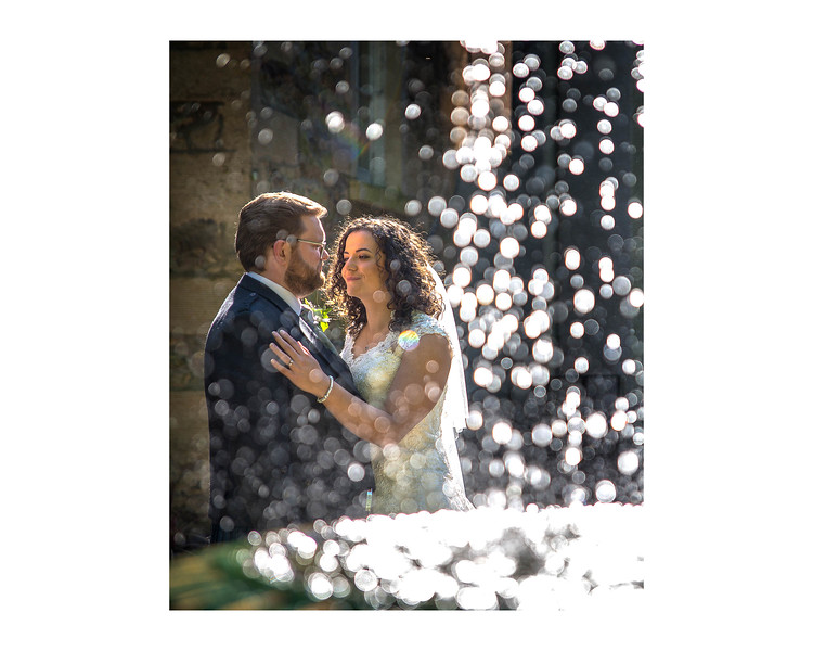 Wedding Photography of Sara & Andrew, Fernie Castle, Cooper, Fife, Photograph is of the Bride & Groom standing in the sun behind a fountain