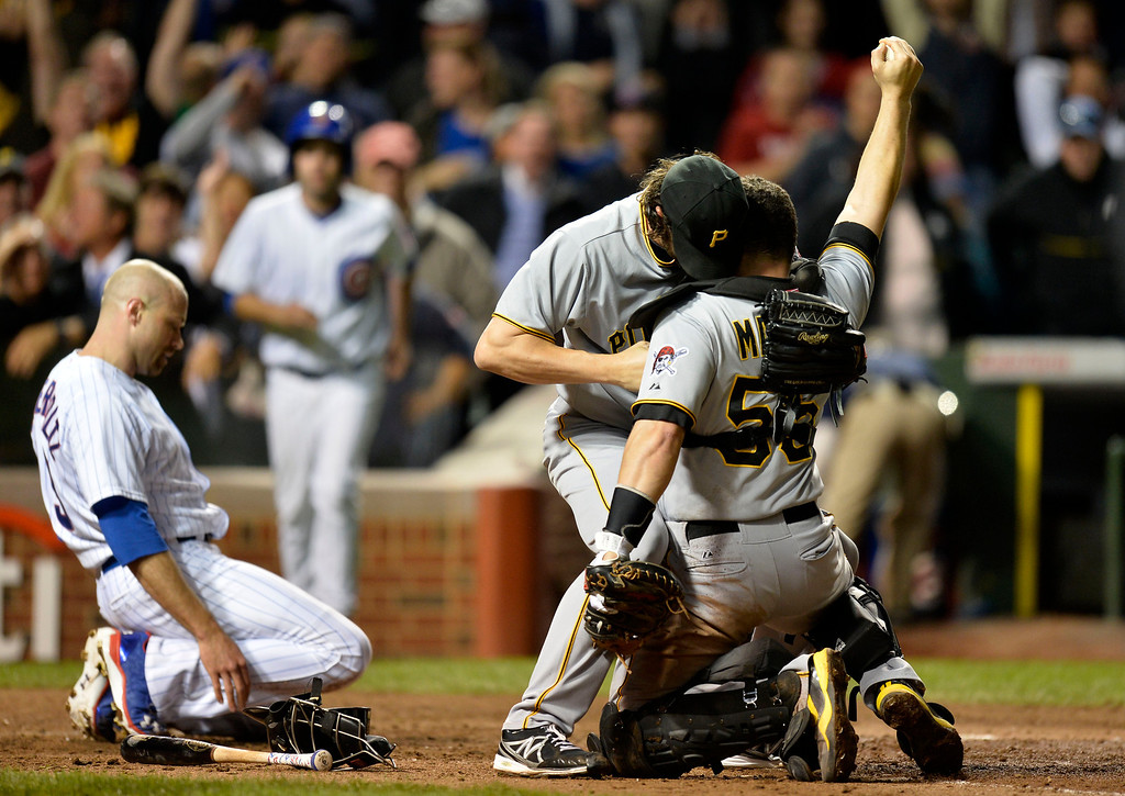 . CHICAGO, IL - SEPTEMBER 23:  Relief pitcher Jason Grilli #39 and catcher Russell Martin #55 of the Pittsburgh Pirates celebrate after Martin tagged Nate Schierholtz #19 of the Chicago Cubs out at home plate for the final out when he tried to score on a single hit by Ryan Sweeney (not pictured)during the ninth inning at Wrigley Field on September 23, 2013 in Chicago, Illinois. The Pirates defeated the Cubs 2-1 and, with their win and a Washington Nationals loss to the St. Louis Cardinals, clinched their first playoff berth in 21 years.  (Photo by Brian Kersey/Getty Images)