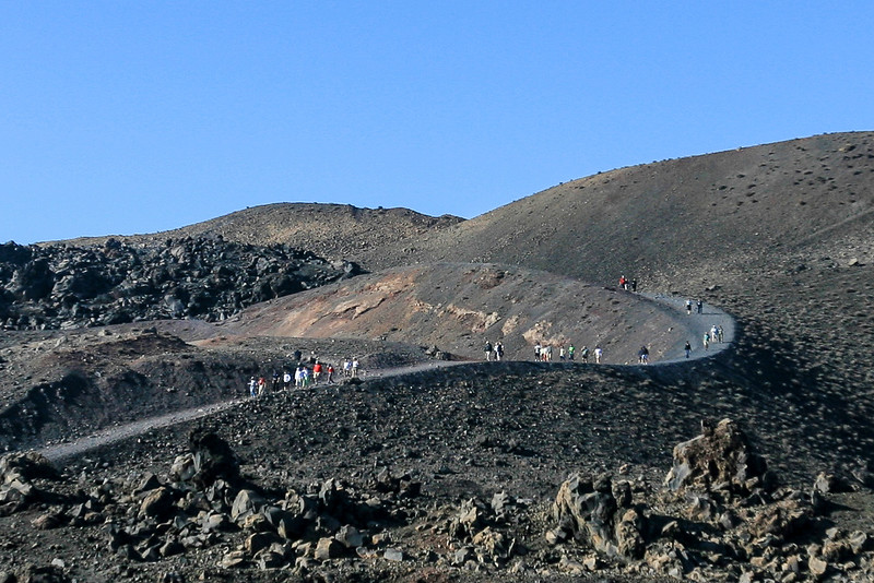 Black volcanic landscape under blue sky on Nea Kameni, Greece