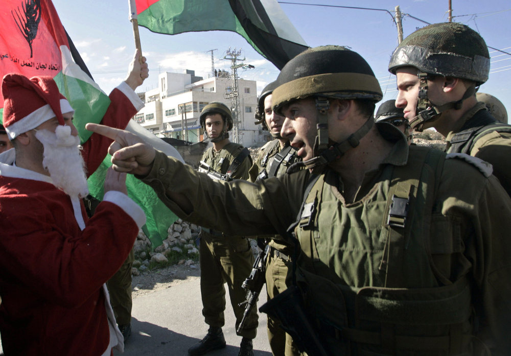 Description of . An Israeli soldier points his finger at journalists as a Palestinian protestor dressed as Santa Claus or Father Christmas holds a Palestinian flag during a demonstration against Israel's separation barrier in the village of Maasarah near the biblical West Bank town of Bethlehem on December 19, 2008. Israel says the barrier, a projected 723 kilometres (454 miles) of steel and concrete walls, fences and barbed wire is needed for security, while Palestinians view it as a land grab that undermines their promised state. AFP PHOTO/MUSA AL-SHAER
