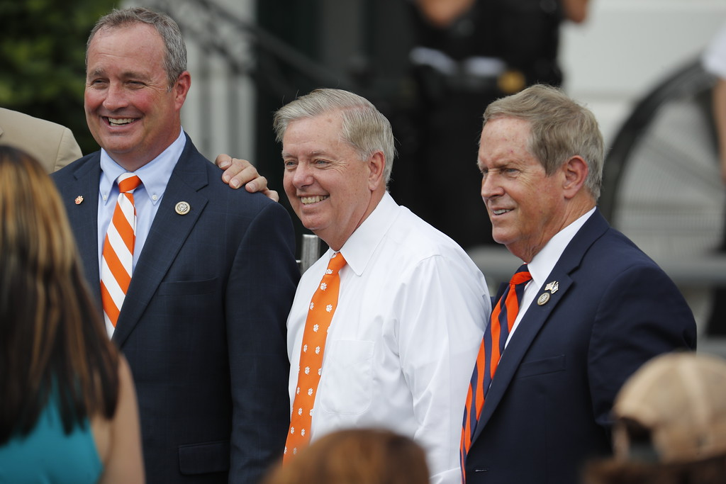 . Sen. Lindsey Graham, R-S.C., center, flanked by Rep. Jeff Duncan, R-S.C., left, and Rep. Joe Wilson, R-S.C., stands on the South Lawn of the White House in Washington, Monday, June 12, 2017, prior to the start of a ceremony where President Donald Trump was to honor the 2016 NCAA Football National Champions Clemson University Tigers. (AP Photo/Pablo Martinez Monsivais)