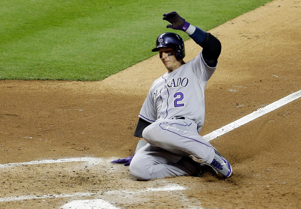 . Colorado Rockies\' Troy Tulowitzki (2) scores on a sacrifice fly by Wilin Rosario in the fourth inning of an MLB National League baseball game against the Miami Marlins, Tuesday, April 1, 2014, in Miami. (AP Photo/Lynne Sladky)
