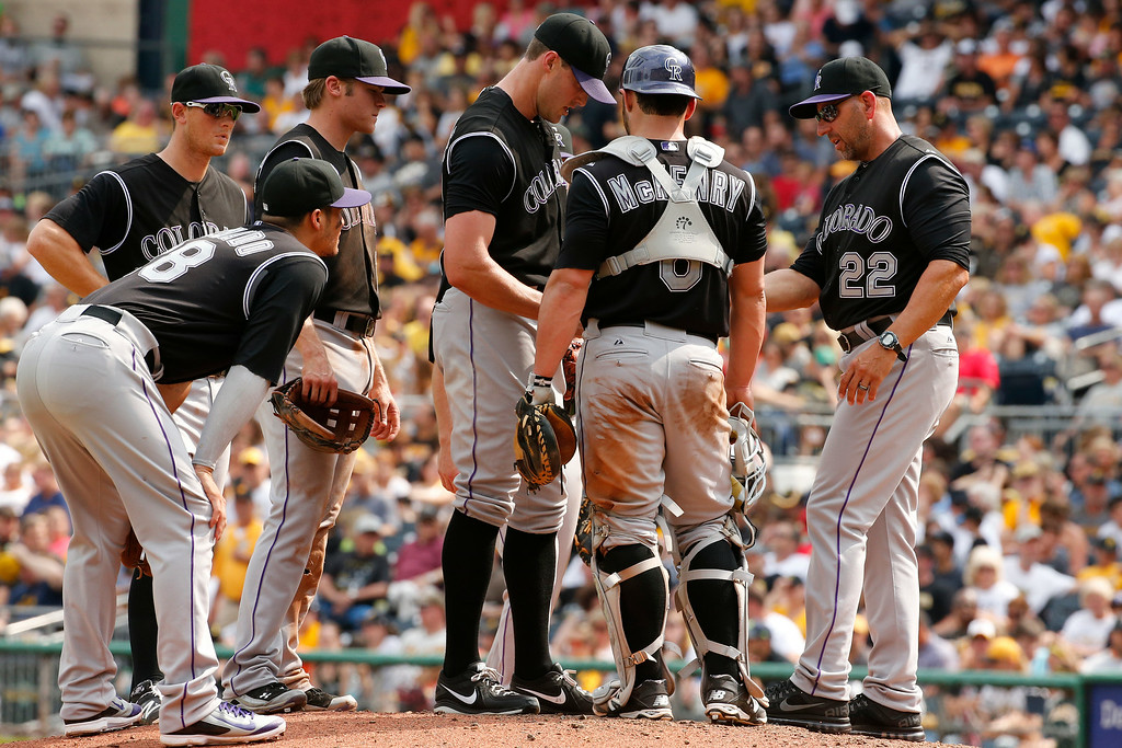 . Colorado Rockies manager Walt Weiss (22) takes the ball from relief pitcher Matt Belisle, center, during the seventh inning of a baseball game against the Pittsburgh Pirates in Pittsburgh Sunday, July 20, 2014. The Pirates won 5-3. (AP Photo/Gene J. Puskar)