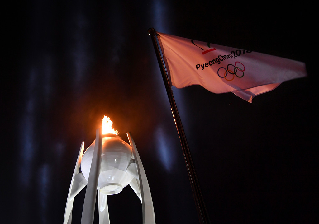 . The Olympic flag waves in front of the Olympic flame just before it was extinguished during the closing ceremony of the 2018 Winter Olympics in Pyeongchang, South Korea, Sunday, Feb. 25, 2018. (Florien Choblet/Pool Photo via AP)