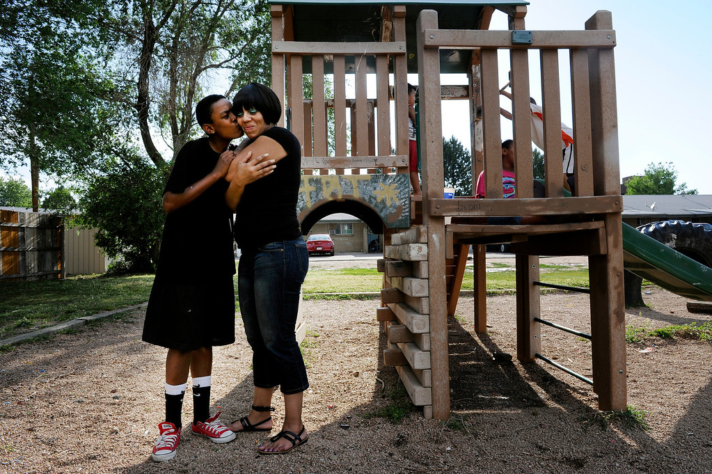 . Isaiah Marquez, 14, kisses his mother Danita Johnson outside their home in Aurora. Johnson is determined to keep her family together and offer her children a better life. �I�ve worked hard and they�re home, so it�s time to move forward,� she said.  �I�m not whole unless I have my kids.� Craig F. Walker, The Denver Post