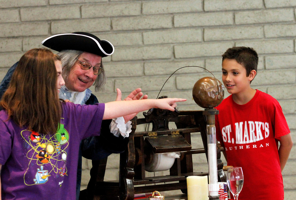 ". Alexis Chernin, 11, left, and Lucas Valero, 10, assist Benjamin Franklin with his ""Electrostatic Generator,\"" during Ben Franklins Colonial Assembly: A Museum On Wheels, at St. Marks Luthern School, in Hacienda Heights, Thursday, March 28, 2013. (Correspondent Photo by James Carbone/HIGH)"
