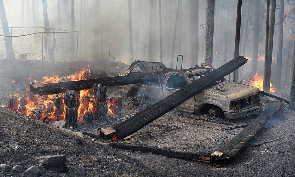. A burned truck and smoldering ruins is all that is left of a garage near a house that burned on Cedar Drive in Oakhurst,  Calif., Sunday, Sept. 14, 2014, as two raging wildfires in the state forced hundreds of people to evacuate their homes. The California Department of Forestry and Fire Protection said flames damaged or destroyed at least 21 structures. (AP Photo/The Fresno Bee, Mark Crosse)