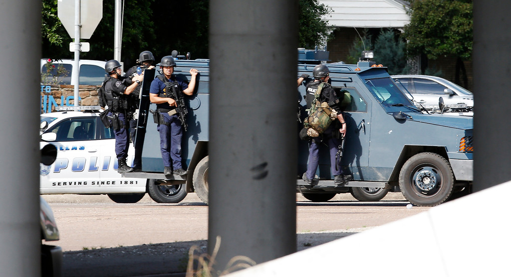 . Tactical officers take up a position at the intersection of Dowdy Ferry Rd and Interstate 45 during a stand off with a gunman barricaded inside a van near by, Saturday, June 13, 2015, in Hutchins, Texas. The gunman allegedly attacked Dallas Police Headquarters. (AP Photo/Brandon Wade)