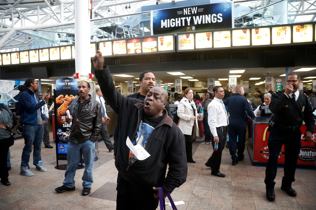 . Activists shout slogans about the minimum wage during a protest at a McDonald\'s restaurant inside the Smithsonian\'s National Air and Space Museum in Washington, Thursday, Dec. 5, 2013. Fast food workers and labor organizers are marching, waving signs, and chanting in cities across the country amid a push for higher wages. (AP Photo/Charles Dharapak)