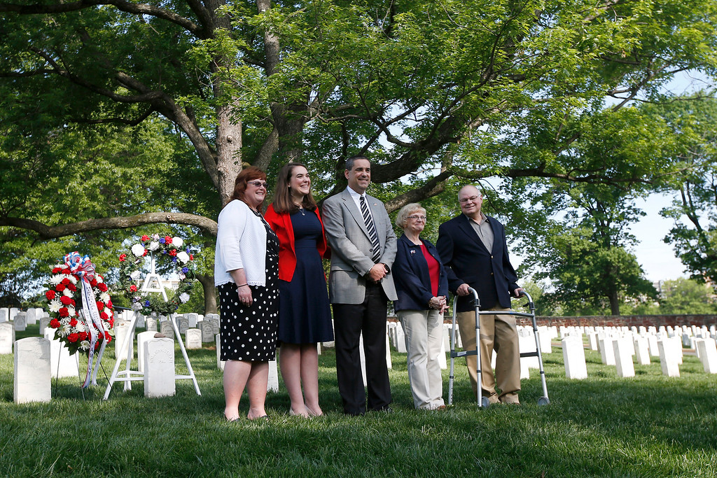 . Relatives of Army Pvt. William Christman, who was the first military burial at the cemetery, James Christman, great-grand nephew, center, his wife Kris, left, and daughter Lauren, second left, from Allentown, Pa., and Barbara Christman Page, great-grand niece, second from right, and her husband Donald Page, from Swiftwater, Pa., stand in front of his grave after they laid a wreath marking the beginning of commemorations of the 150th anniversary of Arlington National Cemetery in Arlington, Va., Tuesday, May 13, 2014, in Arlington, Va. (AP Photo)