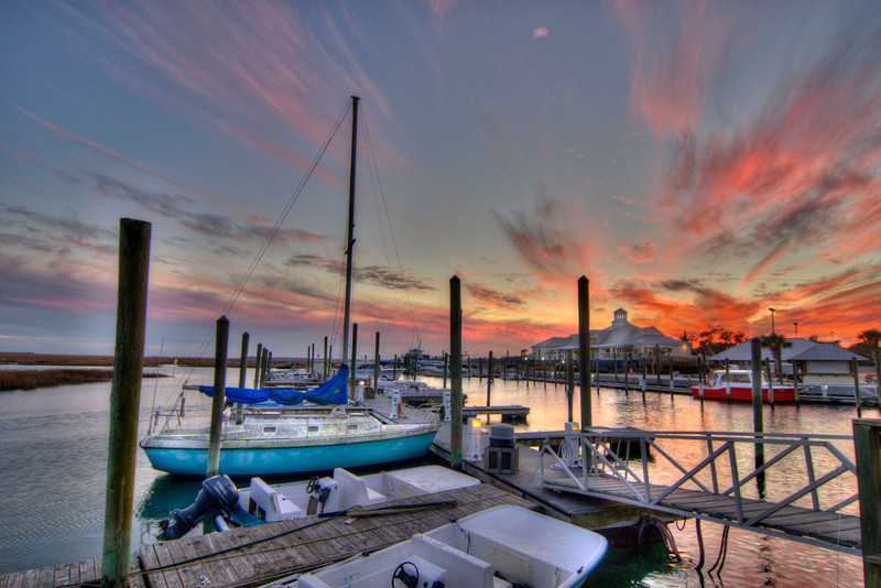 A blue sailboat docked at the Crazy Sister Marina under a dramatic sunset along The Marshwalk in Murrells Inlet, SC on Monday, January 7, 2013. Copyright 2013 Jason Barnette