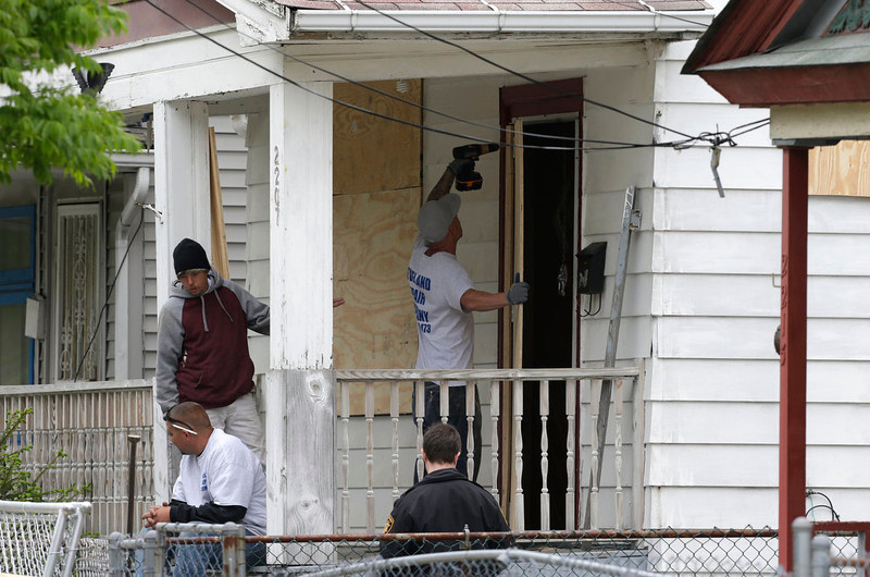 . Workers board up the house Saturday, May 11, 2013 where three women were held in Cleveland on Saturday, May 11, 2013. Suspect Ariel Castro, who allegedly held three women captive for nearly a decade, is charged with rape and kidnapping. (AP Photo/Tony Dejak)