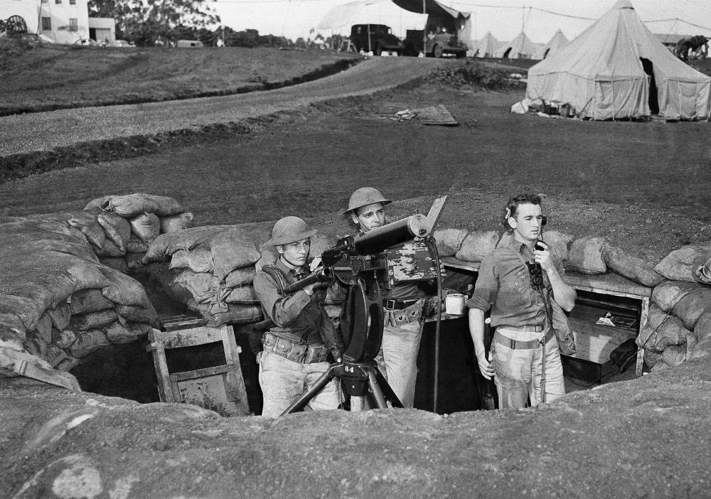Description of . Troops man a machine gun nest at Wheeler Field, which adjoins Schofield Barracks in Honolulu, after the Japanese attack on the island of Oahu, Dec. 7, 1941. (AP Photo)