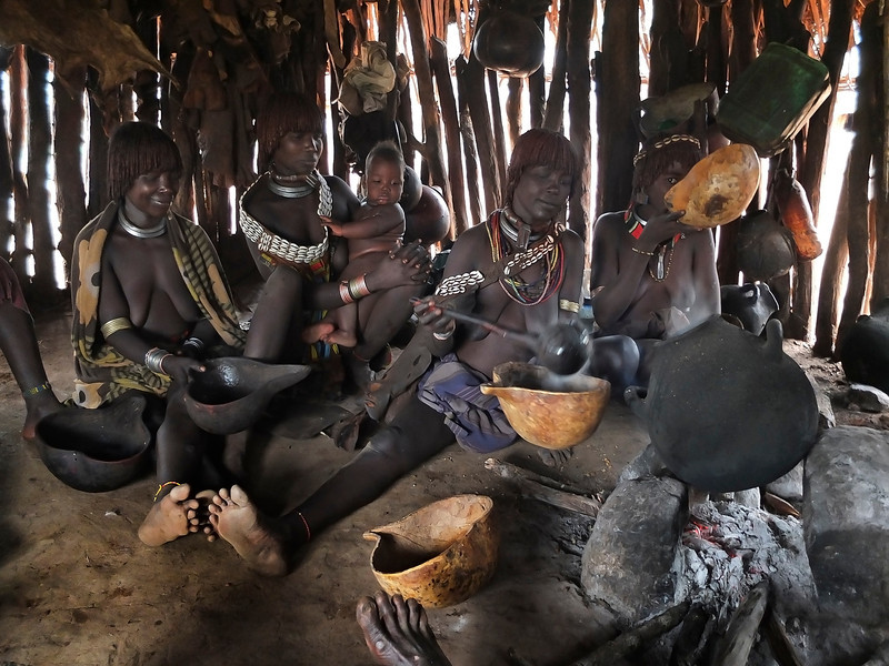 Two Hamer families, including two first wives and two second wives. These two families are having early morning coffee. Coffee is very important for Hamer people and is usually made from the coffee bean shell and not the actual bean. 