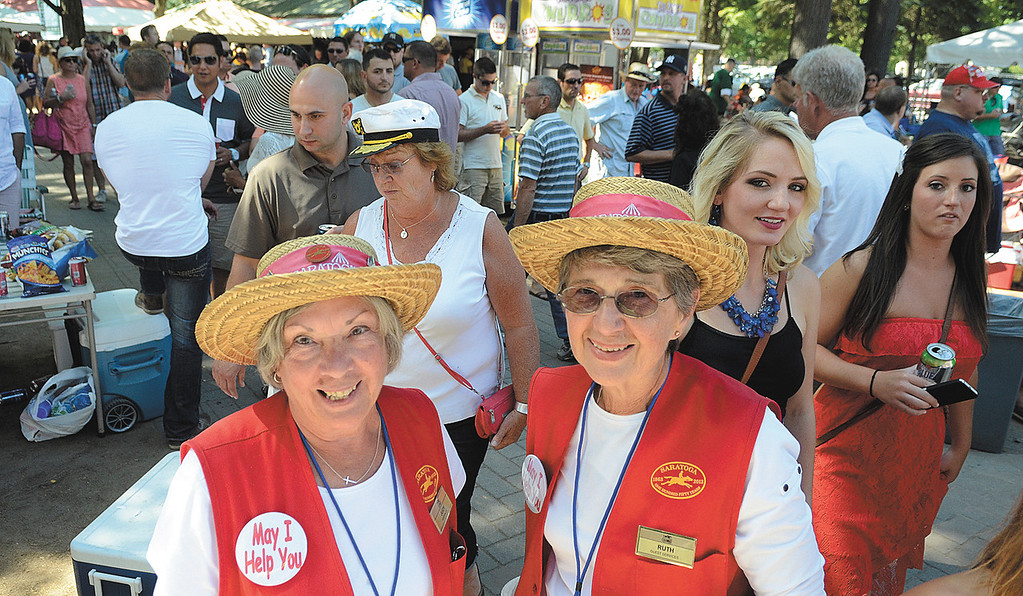 . NYRA hospitality ambassadors Judy Hefter, left, and Ruth Mattiello wait to answer questions from track patrons on Travers day. Photo Ed Burke/SARATOGIAN 8/24/13