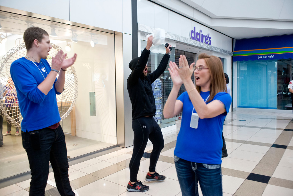 . Rob Beckett, center, of Portland, Mich., is met with cheers and applause as the first person to leave with a brand new iPhone 6 from the Apple Store in Woodland Mall on Friday, Sept. 19, 2014 in Grand Rapids, Mich.  The highly anticipated iPhone 6 and iPhone 6 Plus are being released in stores today. (AP Photo/The Grand Rapids Press, Emily Rose Bennett)