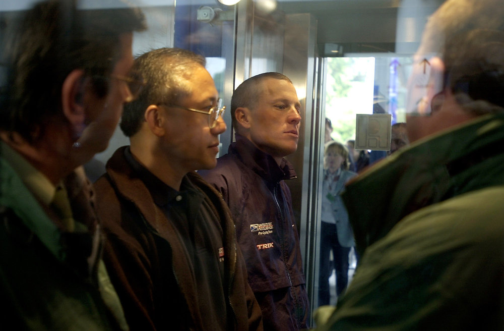 . Three-time Tour de France winner and leader of the U.S. Postal Service cycling team, Lance Armstrong of Austin, Texas, center, is surrounded by race officials as he waits in an elevator upon his arrival at the Tour de France press and medical center, Thursday June 4, 2002 in Luxembourg. Armstrong is to undergo medical examinations and will give a press conference on Thursday, ahead of the Tour de France cycling race due to start next Saturday July 6 from Luxembourg. (AP Photo/Peter Dejong)