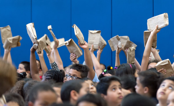 06/01/18 Wesley Bunnell | Staff Students hold up their wrapped books just prior to unwrapping on Friday afternoon at Lincoln Elementary School. The school held their One School, One Book event on Friday afternoon giving every student the same book, The Mouse on the Motorcycle, to bring home to be read with their parents. The books were wrapped with the title kept a secret until being passed out.