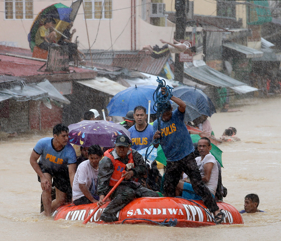 . A man dives in the background as rescuers use a rubber dinghy to rescue trapped residents after continues heavy monsoon rains spawned by tropical storm Fung-Wong flooded Marikina city, east of Manila, Philippines and most parts of  the metropolis Friday, Sept. 19, 2014. (AP Photo/Bullit Marquez)