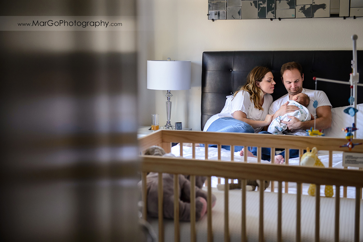 family of three sitting on the bed during newborn session seen through the door