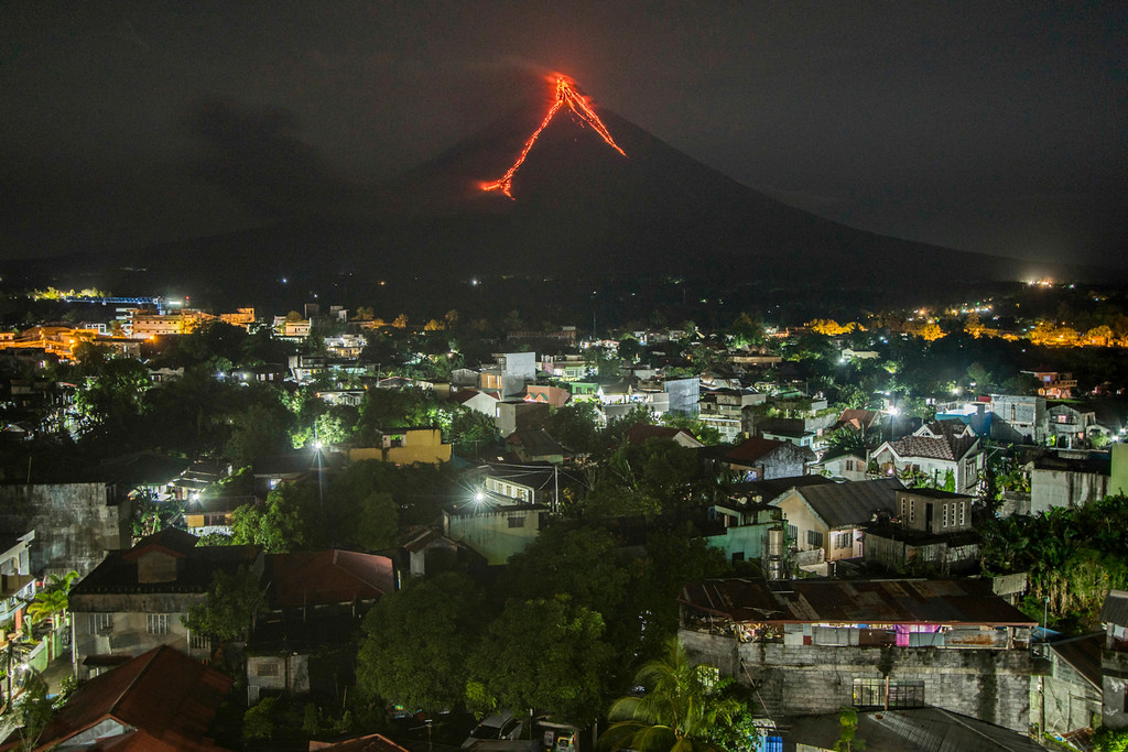 . Lava cascades down the slopes of the Mayon volcano seen from Legazpi city, Albay province, 340 kilometers (210 miles) southeast of Manila, Philippines, Tuesday, Jan. 16, 2018. Over 9,000 people have evacuated the area around the Philippines\' most active volcano as lava flowed down its crater Monday in a gentle eruption that scientists warned could turn explosive. (AP Photo/Dan Amaranto)