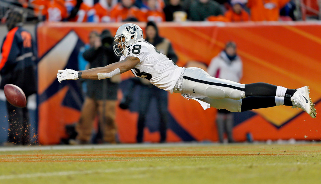 . Oakland Raiders wide receiver Andre Holmes is unable to catch a pass during the second half of an NFL football game against the Denver Broncos, Sunday, Dec. 28, 2014, in Denver. (AP Photo/Joe Mahoney)