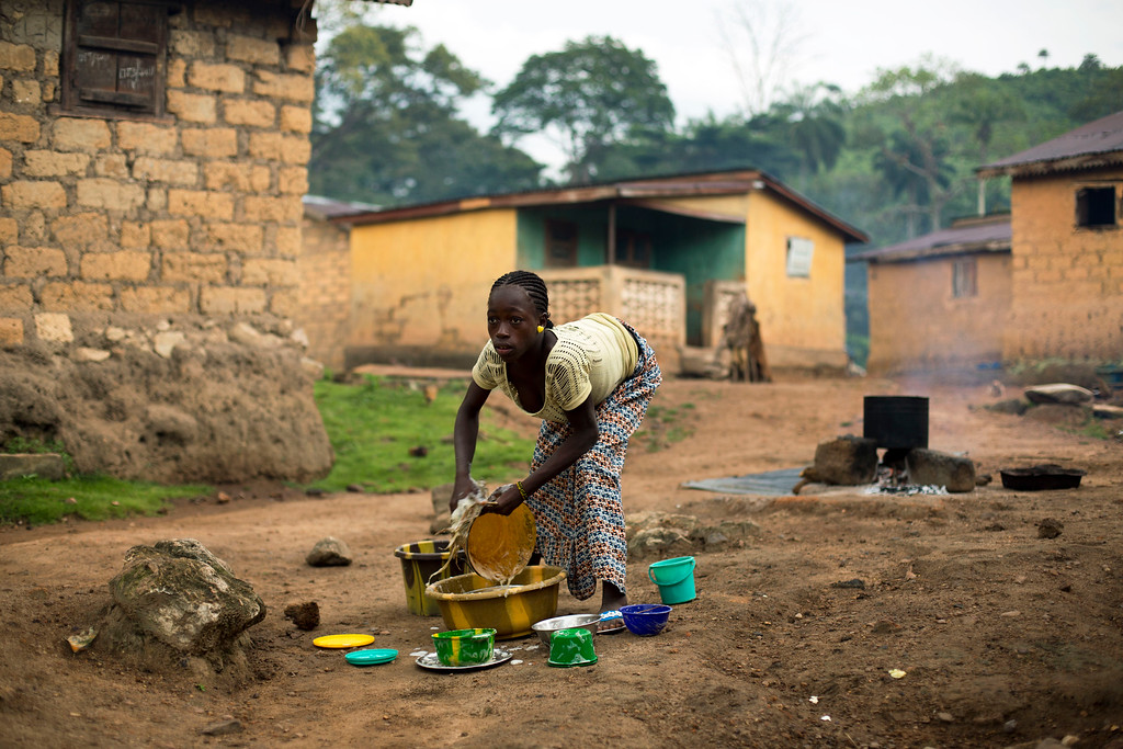 . In this photo taken Sunday Nov. 23, 2014, a young woman washes dishes in the Guinean village of Meliandou, some 400 miles (600 kms) south-east of Conakry, Guinea, believed to be Ebola\'s ground zero. In Meliandou, as in many other villages across Ebola country, the disease is shrouded in mystery, surrounded by suspicion and rumors. People here still believe that Ebola was disseminated by white people seeking the deaths of blacks, including through a measles vaccination campaign; by a laboratory testing bats to create a vaccination against the virus; by politicians from a rival tribe bent on killing off the forest people; by white miners looking to exploit a nearby mountain of iron ore. (AP Photo/Jerome Delay)
