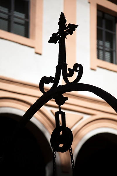 Iron cross and pulley of an old well, cloister of the Fine Arts Museum, Seville, Spain