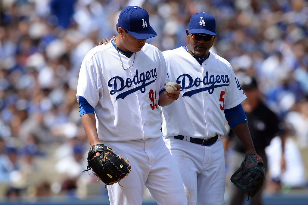 . Dodger pitcher Hyun-Jin Ryu #99 gets some encouragement from Juan Uribe #5 as Ryu struggles early during their home opener at Dodger Stadium Friday 4, 2014. The Giants beat the Dodgers 8-4.  (Photo by Hans Gutknecht/Los Angeles Daily News)