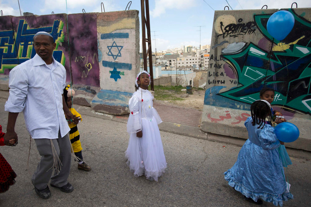 . A Jewish settler walks with children who are dressed in costumes for a parade marking the holiday of Purim in the West Bank city of Hebron February 24, 2013. Purim is a celebration of the Jews\' salvation from genocide in ancient Persia, as recounted in the Book of Esther. REUTERS/Ronen Zvulun