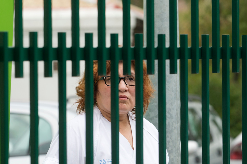 . A hospital staff member looks out from behind the main gate of the Carlos III  hospital in Madrid, Spain, Tuesday, Oct. 7, 2014 where a Spanish nurse who is believed to have contracted the ebola virus from a 69-year-old Spanish priest is being treated after testing positive for the virus. (AP Photo/Paul White)
