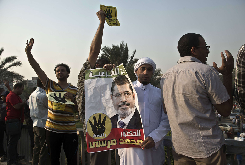 """. Supporters of Egyptian ousted president Mohamed Morsi and of the Muslim brotherhood movement hold posters depicting Morsi and the Rabaa sign during a rally outside the al-Quba presidential palace in Cairo on October 11, 2013. An Islamist alliance urged its supporters to stay away from Cairo\'s Tahrir Square during protests to avoid more bloodshed after a week in which nearly 80 Egyptians were killed. The \""""Rabaa\"""", which means four in Arabic, refers to those killed in the crackdown on the Rabaa al-Adawiya protest camp in Cairo earlier in the year.  KHALED DESOUKI/AFP/Getty Images"""