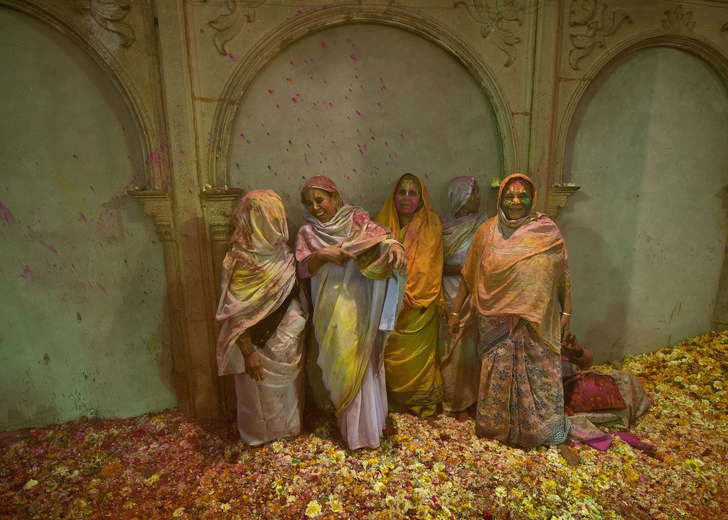 . Indian widows smeared in gulal (colored powder) look on they and others participate in Holi celebrations in Vrindavan on March 14, 2014.  AFP PHOTO/Prakash SINGH/AFP/Getty Images