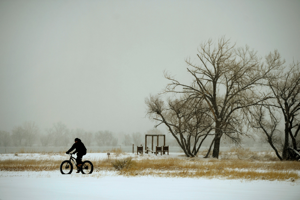 . A bicyclist braves the morning weather  at Crown Hill Park in Lakewood after an over night snow fall left 3 to 6 inches across Denver and the surrounding areas February 21, 2013. Lakewood, Colorado. (Photo By Joe Amon/The Denver Post)