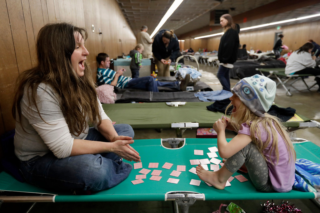 . Katherine Boeger Knight, left, plays a card game with her daughter Amethyst, 5, at a shelter for evacuees from cities surrounding the Oroville Dam, Monday, Feb. 13, 2017, in Chico, Calif. The thousands of people who were ordered to leave their homes after a damaged California spillway threatened to unleash a 30-foot wall of water may not be able to return until significant erosion is repaired, authorities said Monday. (AP Photo/Marcio Jose Sanchez)