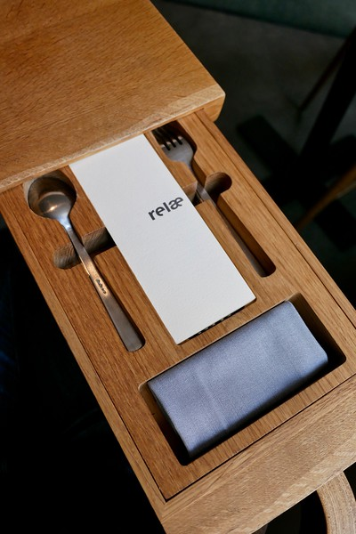 Flatware, menu & napkin custom drawer built into the table. Super cool.