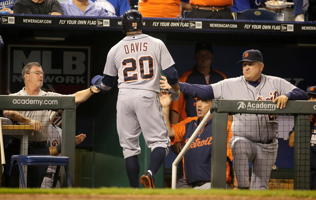 . Detroit Tigers\' Rajai Davis returns to the dugout after scoring on a double by Torii Hunter during the second inning of a baseball game against the Kansas City Royals on Friday, Sept. 19, 2014, in Kansas City, Mo. (AP Photo/Charlie Riedel)