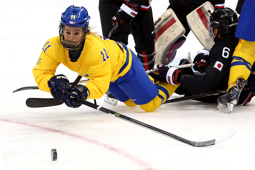. SOCHI, RUSSIA - FEBRUARY 09: Cecilia Ostberg #11 of Sweden tries to control the puck during the Women\'s Ice Hockey Preliminary Round Group B Game on day two of the Sochi 2014 Winter Olympics at Shayba Arena on February 9, 2014 in Sochi, Russia.  (Photo by Martin Rose/Getty Images)