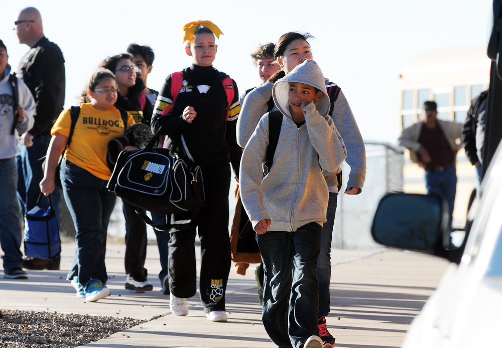 . Students are escorted from Berrendo Middle School after a shooting, Tuesday, Jan. 14, 2014, in Roswell, N.M. A shooter opened fire at the middle school, injuring at least two students before being taken into custody. Roswell police said the school was placed on lockdown. (AP Photo/Roswell Daily Record, Mark Wilson)