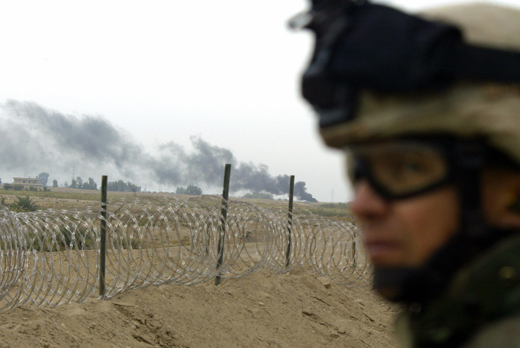 . Smoke billows in the background as a US solider monitors the area, in Fallujah, 50 kms west of Baghdad 08 November 2004. US and Iraqi forces rolled into the insurgent stronghold of Fallujah early today, taking a hospital and two bridges as US warplanes struck rebel targets around the city. AFP PHOTO/PATRICK BAZ  /Getty Images