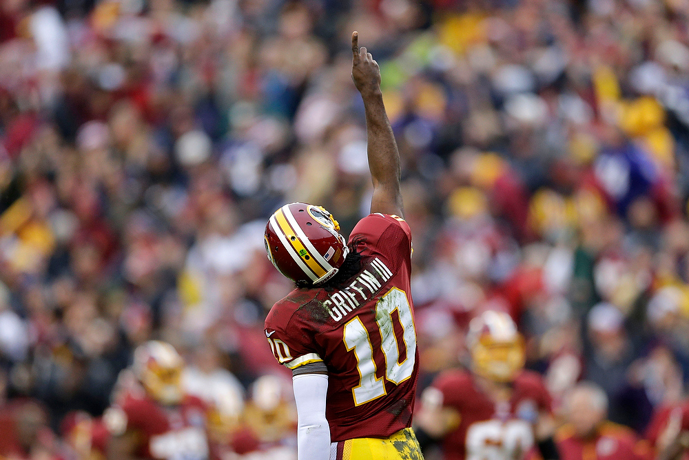 Description of . Washington Redskins quarterback Robert Griffin III reacts to his touchdown pass to wide receiver Josh Morgan during the first half of an NFL football game against the Baltimore Ravens in Landover, Md., Sunday, Dec. 9, 2012. (AP Photo/Patrick Semansky)