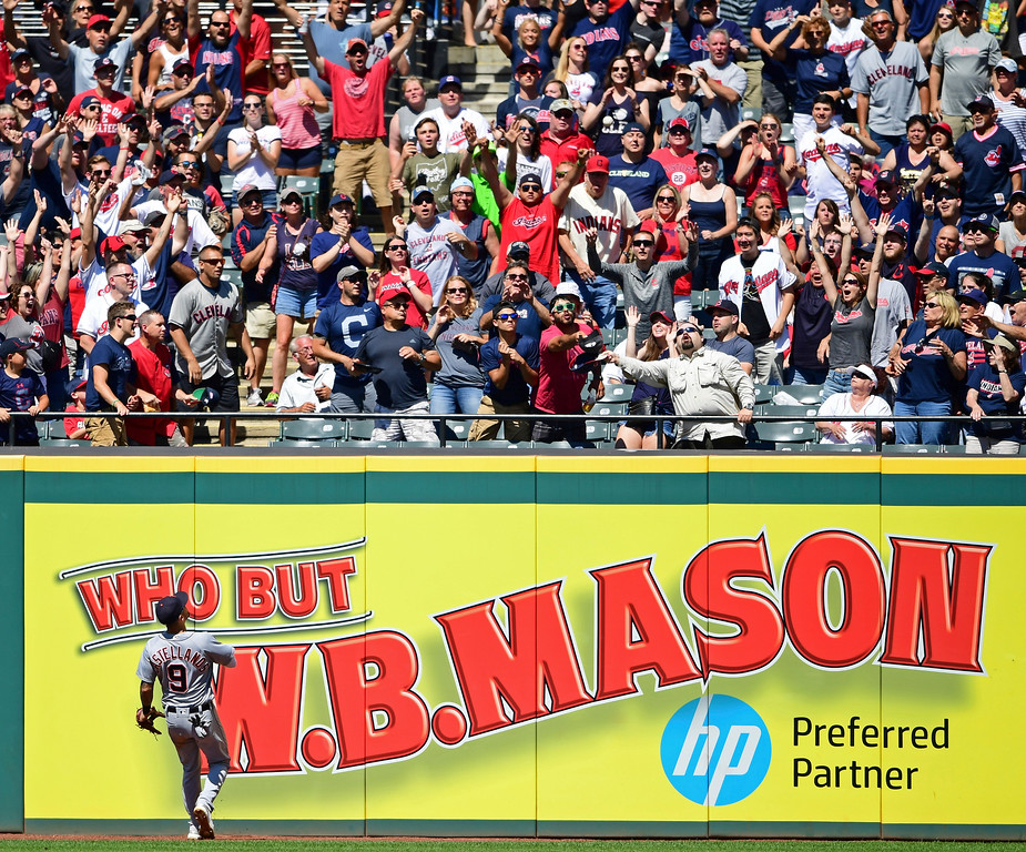 . Fans try to catch Cleveland Indians\' Edwin Encarnacion grand slam ball as Detroit Tigers\' Nicholas Castellanos watches in the eighth inning of a baseball game, Sunday, June 24, 2018, in Cleveland. The Indians won 12-2. (AP Photo/David Dermer)