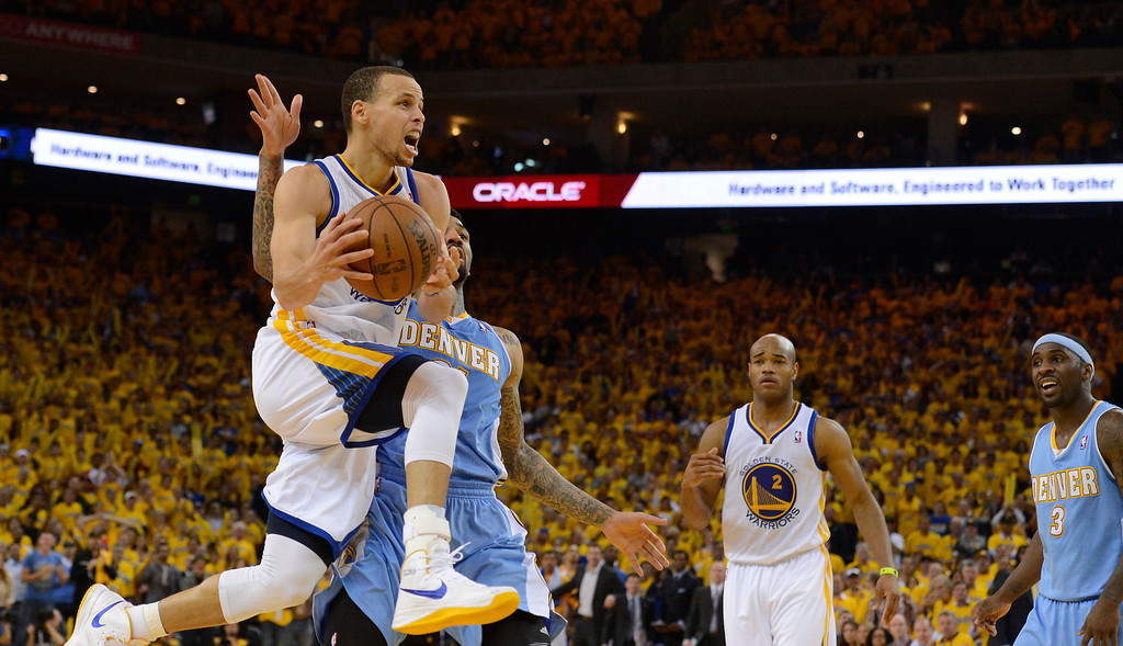 . OAKLAND, CA. - APRIL 26: Stephen Curry (30) of the Golden State Warriors floats through the air past Wilson Chandler (21) of the Denver Nuggets during the third quarter in game 3 of the first round of the NBA Playoffs April 26, 2013 at Oracle Arena.  (Photo By John Leyba/The Denver Post)