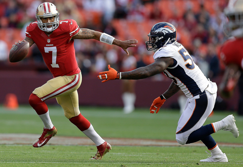 . San Francisco 49ers quarterback Colin Kaepernick, left, runs with the ball away from Denver Broncos outside linebacker Von Miller, right, during the first quarter of an NFL preseason football game on Thursday, Aug. 8, 2013, in San Francisco. (AP Photo/Ben Margot)